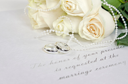 silver jewelry: wedding rings and roses on formal wedding invitation