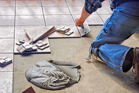 tile flooring: man laying ceramic floor tile Stock Photo