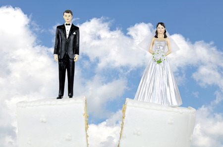 bride and groom on split wedding cake tier with sky