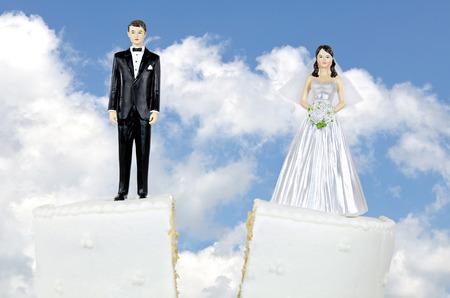 Novia y el novio en la división de pastel de bodas con cielo