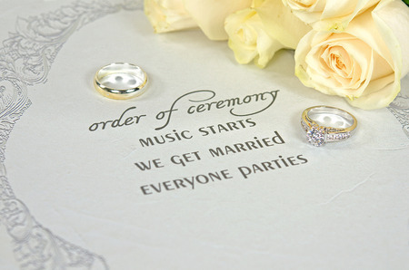 silver frame: rings on a contemporary wedding invitation