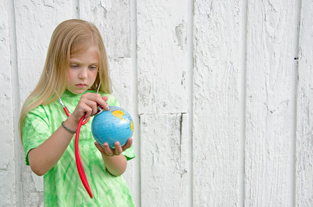 little girl with stethoscope on a world globe photo