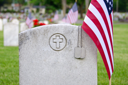 tribute: dog taqs on veteran s tombstone with flag Stock Photo