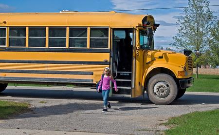 autobus escolar: chica de bajarse del autobús escolar Foto de archivo
