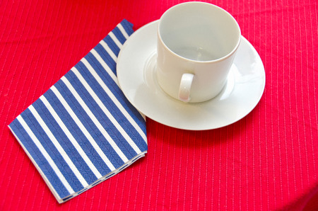 Empty coffee cup with striped napkin on red tablecloth Stock Photo