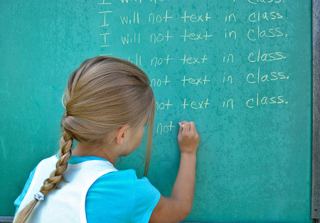 writing lines: little girl writing lines on green chalkboard