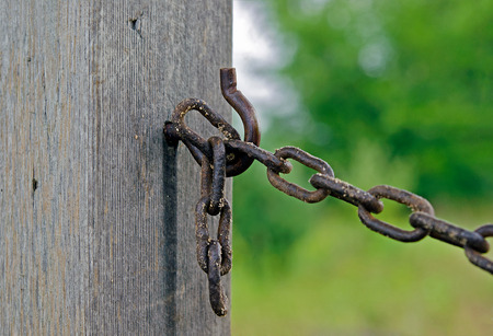 rusty chain on a hook on wooden post Stock Photo
