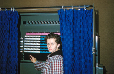 woman in voting booth with blue curtain
