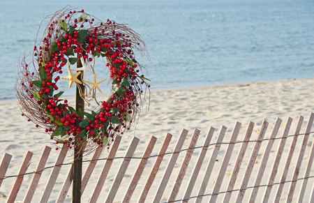 Christmas berry wreath with starfish on beach fence Standard-Bild