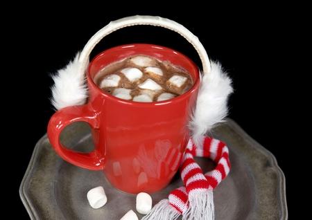 furry white ear muffs on a mug of hot chocolate