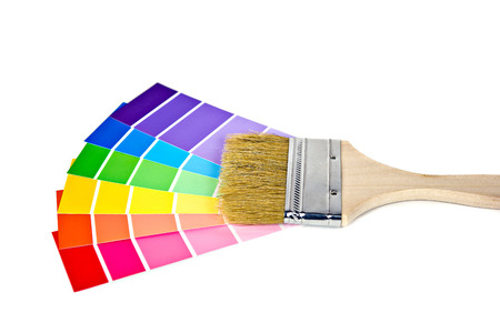 paint brush on colorful paint chips isolated on white photo