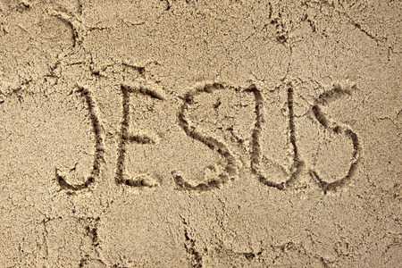 written: name Jesus written in beach sand