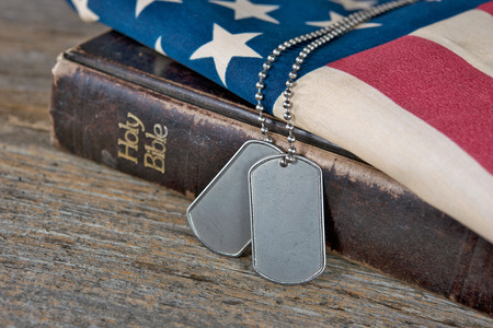 military dog tags on Bible and American flag Stock Photo