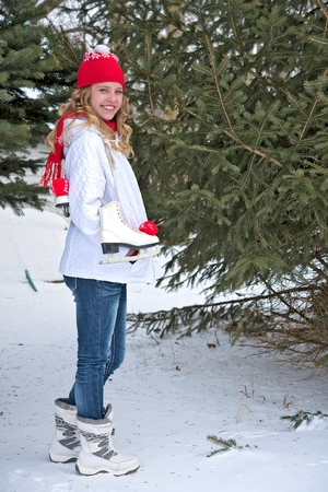 skating on thin ice: young teenage girl with ice skates in winter woods