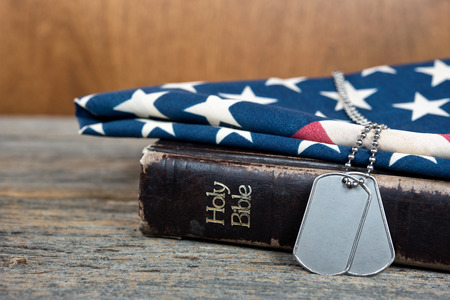 military dog tags on worn Bible and American flag Foto de archivo