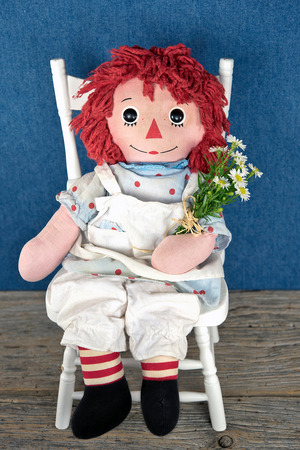old rag doll with daisy bouquet
