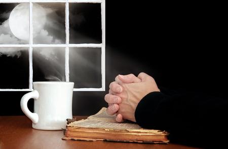 moonbeam: praying hands on worn old Bible in moonlight Stock Photo