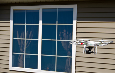 airborne vehicle: drone hovering by window of a residential house Stock Photo