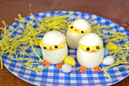 pascuas navide�as: Pollitos de Pascua Huevos rellenos en la placa a cuadros azul y blanco Foto de archivo