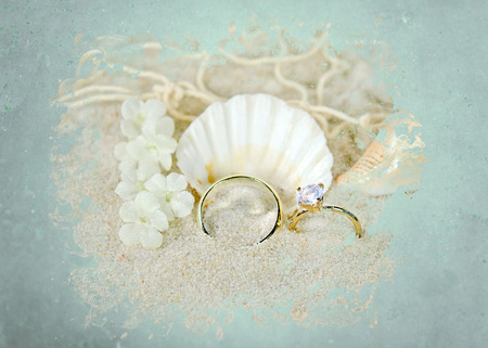 wedding rings and seashell in sand with aqua texture border photo