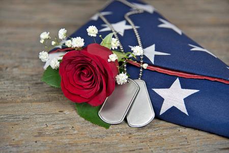 estrellas  de militares: rosa roja y etiquetas de perro militares en bandera doblada