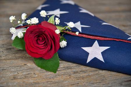 Rode roos in gevouwen Amerikaanse vlag op rustiek hout Stockfoto