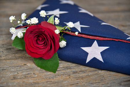 red rose in folded American flag on rustic wood Standard-Bild