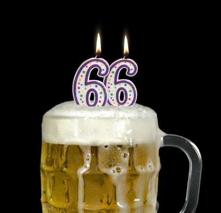 vasos de cerveza: velas en la cerveza para 66 cumpleaños Foto de archivo