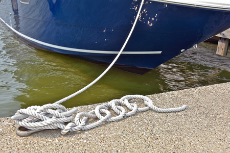 cleat: nautical rope tied to cleat securing boat in marina slip Stock Photo