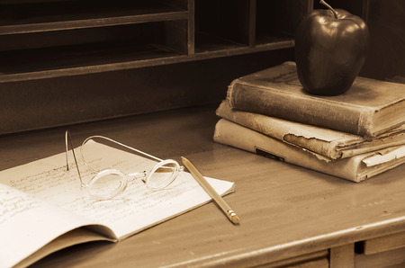 vintage furniture: old-fashioned eye glasses on teachers desk with books