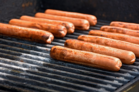 grill: row of beef hot dogs cooking on barbecue grill