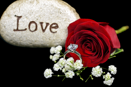 diamond engagement ring with red rose and rock Stock Photo