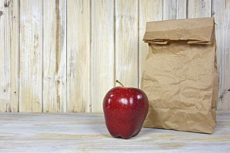 apple sack: brown paper sack and red apple on whitewashed wood