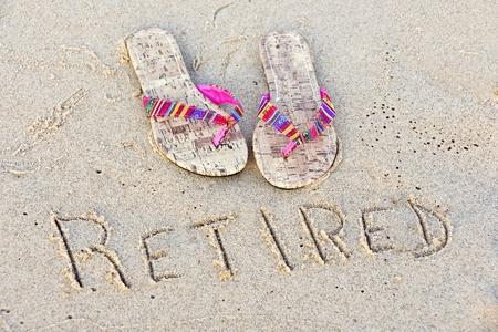 flipflops: flip-flops in sand with retirement sign