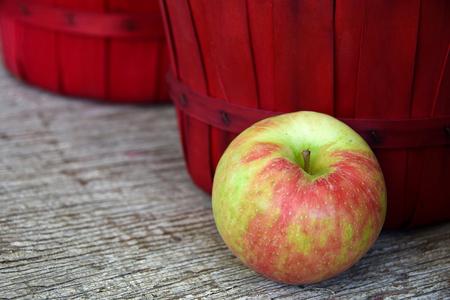 bushel: apple and red bushel basket on weathered wood
