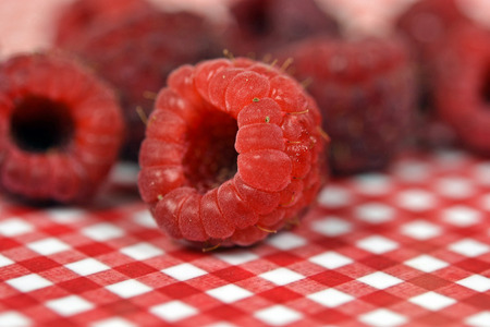 close up of ripe raspberries on red and white checkered plate Stock Photo