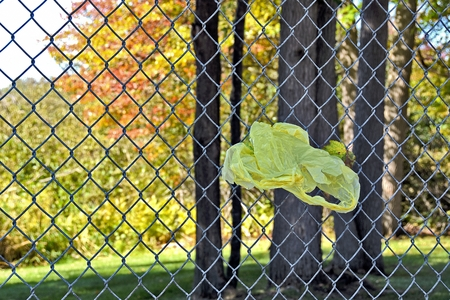 chain link fence: yellow plastic shopping sack in chain link fence Stock Photo