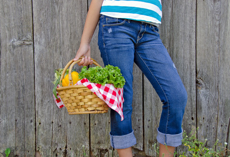 young  cuffs: girl holding a basket of lettuce and peppers Stock Photo