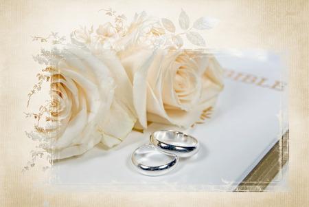 trouwringen en rozen op Bijbel met elegante maskerframe Stockfoto