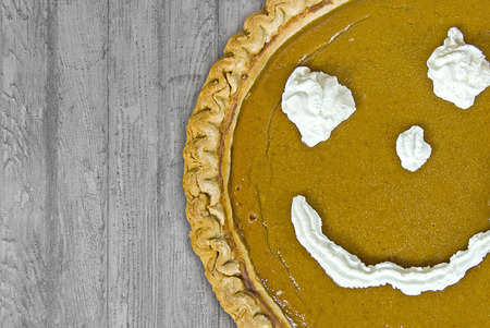 whipped cream: pumpkin pie with whipped cream happy face on rustic wood