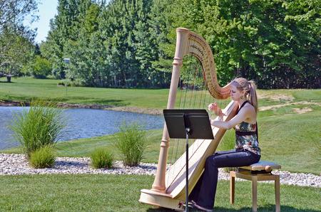 the harp: mujer joven tocando un arpa por la charca rural