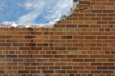 barrier: crumbling brick wall with wispy clouds in blue sky