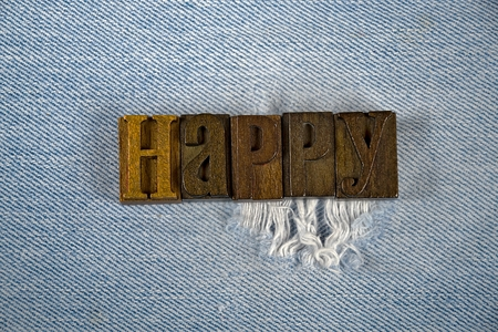 letterpress type: word happy in vintage letterpress type on frayed denim fabric Stock Photo