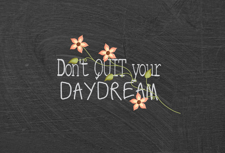 encouragement: daydream quote with flowers on dusty black chalkboard Stock Photo