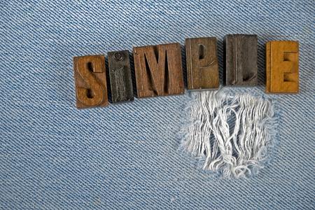 letterpress type: word simple in vintage letterpress type on frayed denim fabric