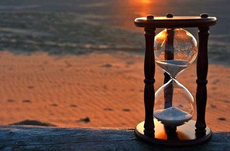 sand timer on beach log with sunset glow Stock Photo