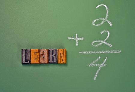 letterpress type: word learn in vintage wooden letterpress type on chalkboard with simple math Stock Photo
