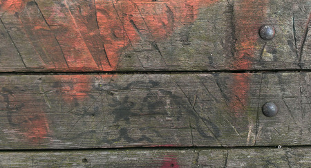 defaced: faded orange spray paint on weathered wood with rivets