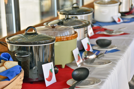 row of crock pots in chili cook off contest in restaurant