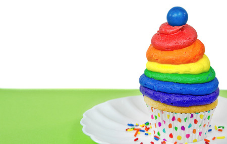 gumball: rainbow cupcake with blue gumball and sprinkles Stock Photo